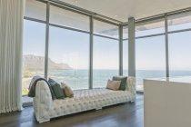 Тафтинговые шезлонги на роскошные дома витрина интерьера окна с видом на океан — стоковое фото
