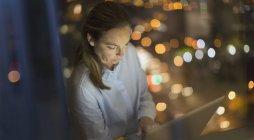 Femme d'affaires sérieuse et concentrée travaillant tard à l'ordinateur portable dans la fenêtre du bureau la nuit — Photo de stock