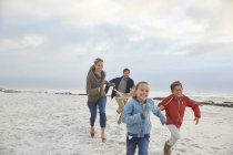 Playful family running on winter beach — Stock Photo