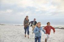 Juguetona familia corriendo en la playa de invierno - foto de stock