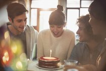 Young adult friends celebrating birthday with cake and candle — Stock Photo