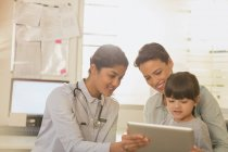 Female pediatrician showing digital tablet to girl patient and mother in examination room — Stock Photo