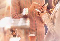 Mann und Frau SMS mit Handy und Biertrinken in Bar — Stockfoto