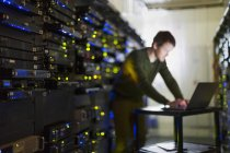 Server room technician working at laptop in corridor — Stock Photo