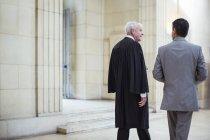 Суддя і адвокат, проходячи через courthouse разом — стокове фото