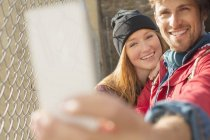 Couple taking self-portrait with camera phone next to chain link fence — Stock Photo