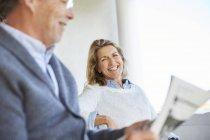 Smiling senior couple reading newspaper on patio — Stockfoto