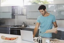 Man with newspaper using laptop in kitchen — Stock Photo