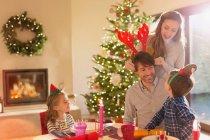 Сім'я, носити Роги оленя ельф і костюм Різдво обіднім столом — стокове фото