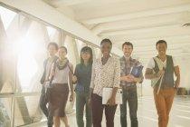 Des gens d'affaires créatifs confiants marchant dans un couloir ensoleillé — Photo de stock