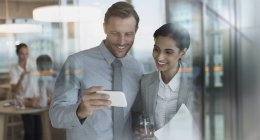 Smiling businessman and businesswoman watching video on smart phone in office — Stock Photo