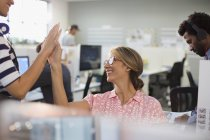 Enthusiastic, confident businesswomen high-fiving in office — Stock Photo