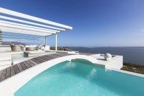 Sunny tranquilla casa vetrina piscina a sfioro esterna con vista sull'oceano sotto il cielo blu — Foto stock