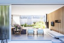 Sliding glass door opening to modern living room — Stock Photo