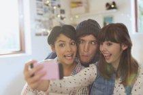Amigos jóvenes juguetones tomando selfie haciendo caras tontas - foto de stock