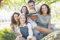 Happy modern family hugging outdoors at picnic — Stock Photo
