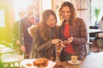 Femmes amis utilisant le téléphone cellulaire dans le café — Photo de stock