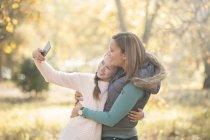Мать и дочь делают селфи на открытом воздухе — стоковое фото