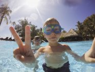 Portrait of boy gesturing peace sign in tropical swimming pool — Stock Photo