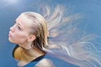 Ritratto bello adolescente biondo con capelli lunghi che galleggia nella piscina — Foto stock