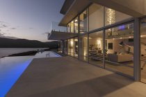 Tranquil modern luxury home showcase exterior with lap pool and dusk ocean view — Stock Photo