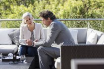 Businessman and businesswoman using digital tablet on balcony patio sofa — Stock Photo