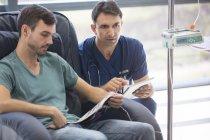 Médico segurando comprimido digital, conversando com paciente em tratamento médico no hospital — Fotografia de Stock