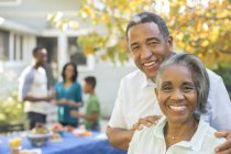 Portrait of smiling senior couple at barbecue — Stock Photo
