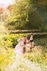 Хлопчик і дівчинка брат і сестра, граючи з шланга у Сонячний Літній сад — стокове фото