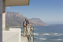 Couple looking at sunny ocean view from luxury balcony — Stock Photo