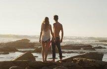 Молодая пара, взявшись за руки и глядя на океан — стоковое фото