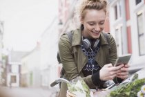 Sorrindo jovem mensagens de texto com telefone celular na bicicleta na rua da cidade — Fotografia de Stock