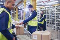 Trabalhadores de digitalização e processamento de caixas na correia transportadora em armazém de distribuição — Fotografia de Stock