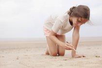 Fille avec bâton écriture dans le sable sur la plage d'été couvert — Photo de stock
