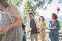 Família moderna feliz movendo pratos da mesa ao ar livre — Fotografia de Stock