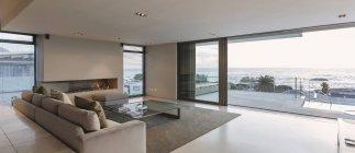 Moderna casa de luxo vitrine sala de estar com portas de pátio abertas para vista para o mar e pátio — Fotografia de Stock