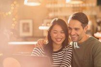 Lächelnde paar Video-Chats mit Laptop im café — Stockfoto