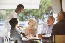 Офіціант, подачі їжі для пари в ресторані таблиці — стокове фото