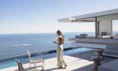 Woman walking and texting with smart phone on sunny modern, luxury home showcase patio with ocean view — Stock Photo