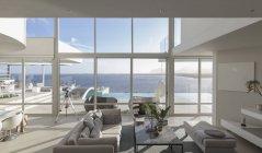 Luxo moderno ensolarada e tranquila casa vitrine interior sala de estar com vista para o pátio e o oceano — Fotografia de Stock