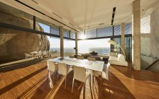 Sun shining in modern luxury home showcase dining room with ocean view — Stock Photo