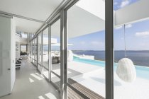 Modern luxury home showcase windows with infinity pool and ocean view — Stock Photo