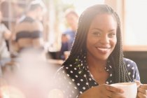 Portrait smiling African woman drinking cappuccino in cafe — Stock Photo