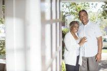 Портрет улыбающейся пожилой пары в дверях — стоковое фото
