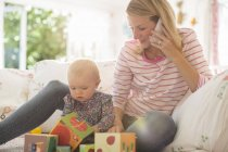 Mother with baby girl talking on pphone — Stockfoto