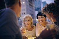 Улыбающиеся пары пьют белое вино и разговаривают в городском кафе — стоковое фото