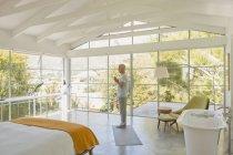 Зрілою людиною практикуючих йогу руками в центр серця в сучасні спальні зі склепінчастою дерев'яні балки на стелі — стокове фото
