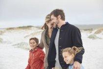Счастливая семья, гуляющая по зимнему пляжу — стоковое фото