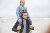 Father carrying daughter on shoulders on winter beach — Stock Photo