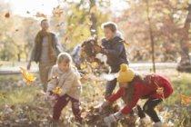 Famiglia che gioca in foglie di autunno a parco — Foto stock
